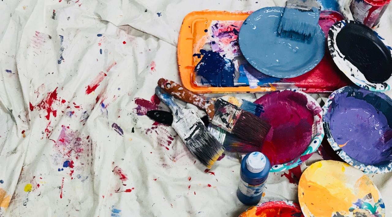 Des seaux de peinture ouverts, des pinceaux, le tout sur une bâche en tissu avec des tâches de couleur