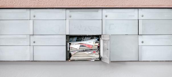 Des boîtes aux lettres, dont une est ouverte et pleine de journaux