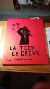 Tableau rouge avec, en noir, un poing levé tenant des câbles RJ45, le texte « La tech en grève » et l'adresse https://onestla.tech